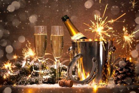 Foto de Fondo de celebración de año nuevo con par de flautas y botella de champagne en balde y una herradura como amuleto - Imagen libre de derechos