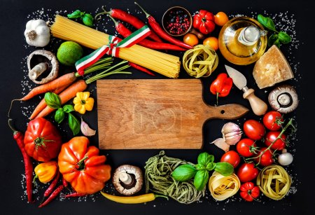 Photo for Italian cuisine. Vegetables, oil, spices and pasta on dark background - Royalty Free Image