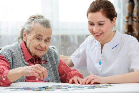 Photo pour Infirmière de soins aux aînés jouant au puzzle avec une femme âgée dans une maison de soins infirmiers - image libre de droit