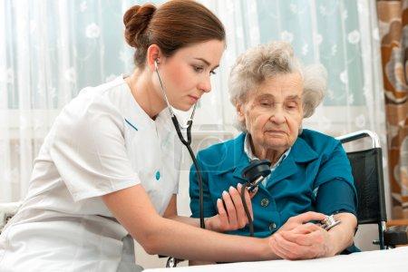 Measuring blood pressure of senior woman
