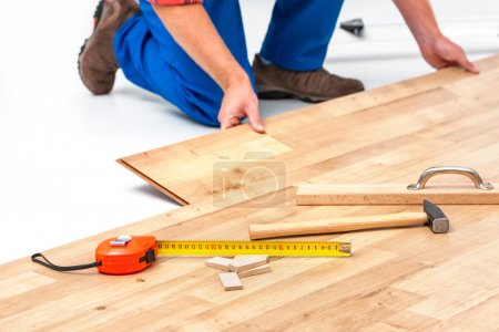 Photo for Carpenter worker installing laminate flooring in the room - Royalty Free Image