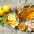 Cup of ginger tea with honey and lemon on wooden t...