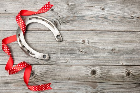Photo for Holidays background with horseshoe and red ribbon on old wooden - Royalty Free Image