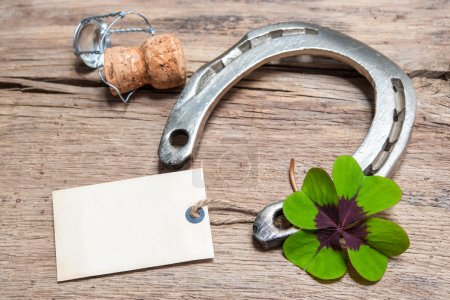 Photo for Horseshoe, shamrock and champagne cork with empty tag on old wooden - Royalty Free Image