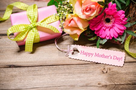 Photo pour Bunch of flowers and tag with text on wooden background. Happy Mothers Day - image libre de droit