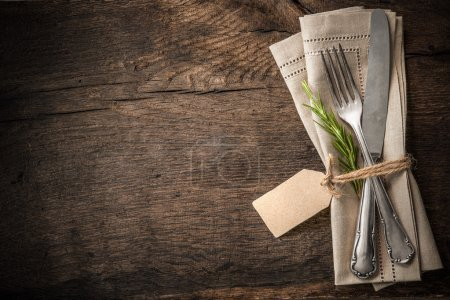 Photo for Vintage silverware with a twig of rosemary and empty tag on rustic wooden background - Royalty Free Image