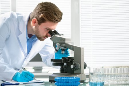 Photo for Scientist looking through a microscope in a laboratory - Royalty Free Image