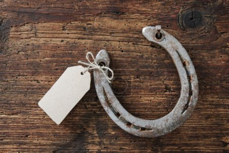 Photo for Horseshoe with an empty tag on wooden board - Royalty Free Image