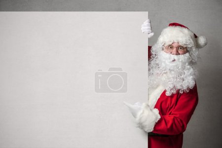 Photo for Santa Claus pointing in blank sign - Royalty Free Image