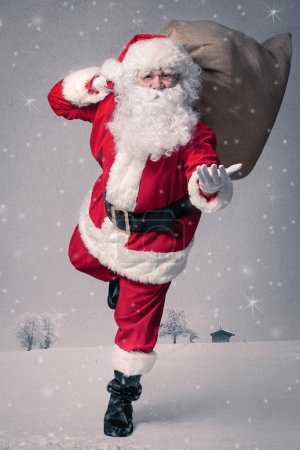 Photo for Santa Claus running with the bag of the presents - Royalty Free Image