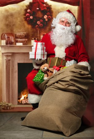 Photo for Santa Claus with a bag full of presents having a rest at the fireplace - Royalty Free Image