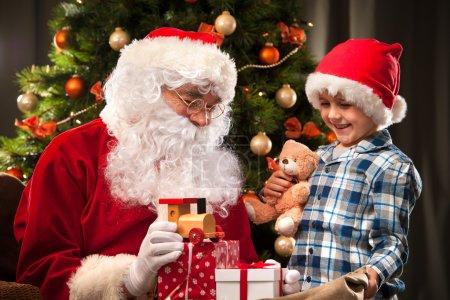 Photo pour Père Noël et un petit garçon. Garçon tenant des cadeaux devant l'arbre de Noël - image libre de droit