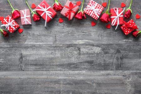 Photo pour Fond vintage Saint Valentin avec des roses rouges et des boîtes-cadeaux sur une planche en bois - image libre de droit