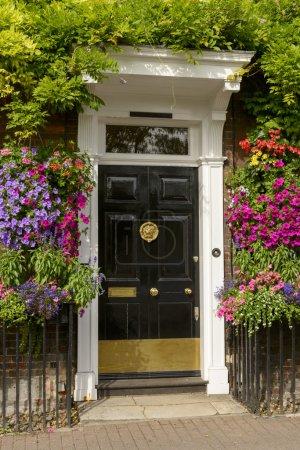 Photo pour Fleurs florissantes et verdure autour de la porte géorgienne d'une vieille maison façade en brique, tourné dans un village touristique sur la Tamise - image libre de droit