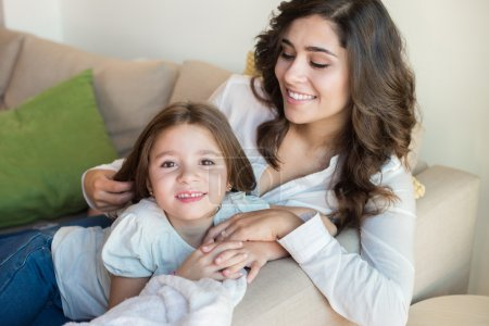 Photo for Mother and daughter relaxing together on couch - Royalty Free Image