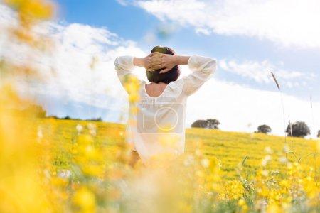 Photo pour Vue arrière d'une femme dans le domaine jaune - image libre de droit