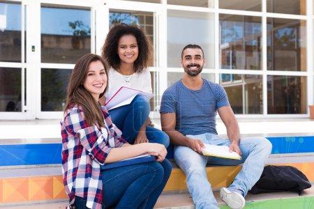 Photo pour Groupe d'étudiants assis sur les escaliers de l'école - image libre de droit