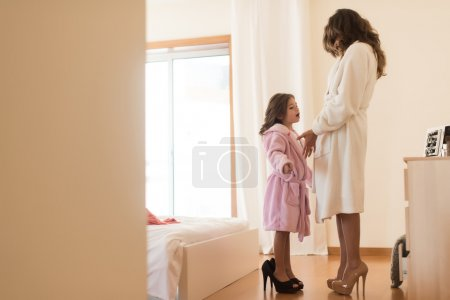 girl wearing heels with mother