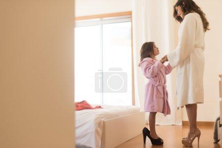 Photo pour Petite fille portant des talons avec sa mère dans la chambre - image libre de droit