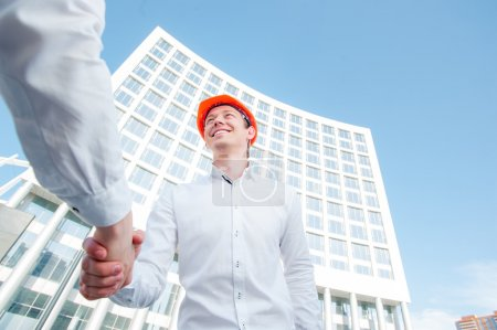 Photo for Builder shaking partner hand against new structure - Royalty Free Image