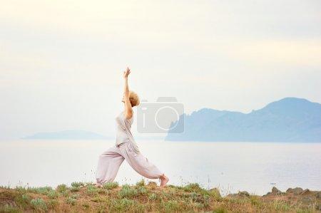 Photo pour Femme âgée faisant des exercices de yoga avec la montagne sur le fond - image libre de droit