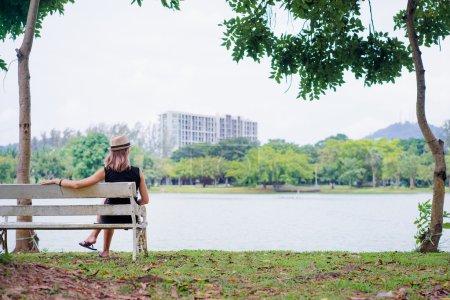 Photo pour Jeune femme en chapeau assise sur le banc du parc près du lac . - image libre de droit
