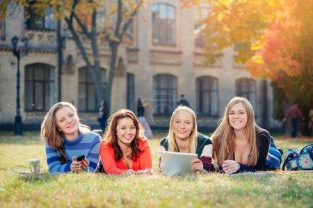 Photo pour Groupe de quatre jeunes étudiantes heureuses souriantes couchées sur l'herbe du campus - image libre de droit