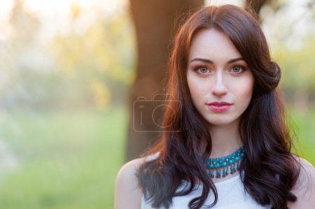 Photo for Outdoors portrait of beautiful young brunette woman looking at camera. - Royalty Free Image
