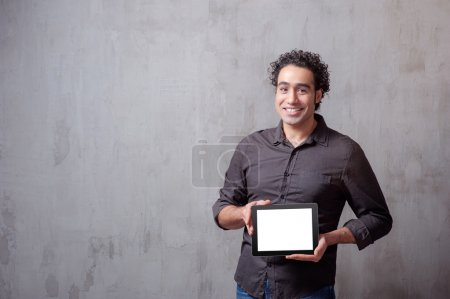 Photo for Cheerful young man holding a digital tablet and smiling while standing against grey background - Royalty Free Image