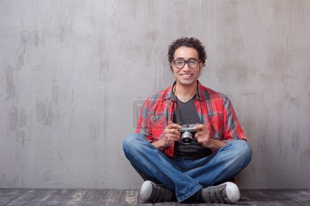 Photo for Handsome young Afro-American hipster holding camera and smiling while sitting against grey background - Royalty Free Image