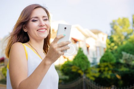 Photo for Youth and technology. Attractive young woman using smartphone outdoors. - Royalty Free Image