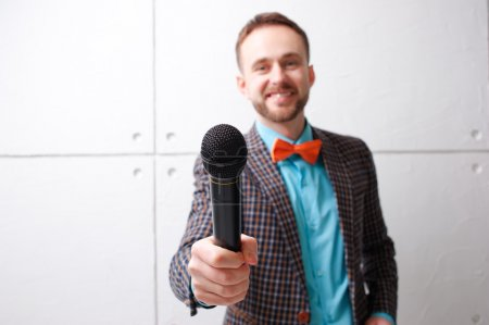 Man in plaid suit with microphone.