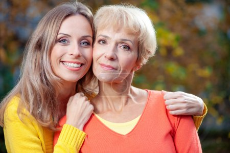 Photo for Portrait of pretty middle aged Mother with her smiling adult daughter looking at the camera in the garden - Royalty Free Image