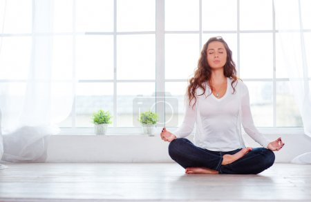 Young woman sitting on lotus position
