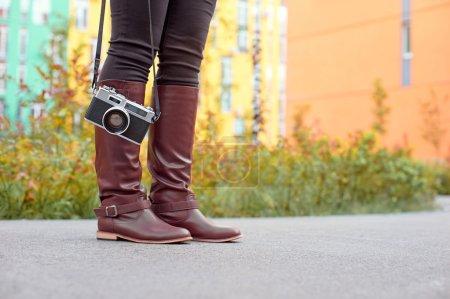 Female feet and vintage photo camera