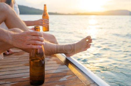 Photo pour Fête avec des amis. Gros plan main masculine tenant bouteille de bière sur le yacht naviguant sur la mer . - image libre de droit