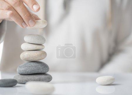 Photo pour Image horizontale d'un homme empilant des cailloux sur une table avec un espace de copie pour le texte. Concept de développement personnel ou de réalisation de soi . - image libre de droit