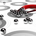 Horseshoe magnet attracting metal balls in the cen...