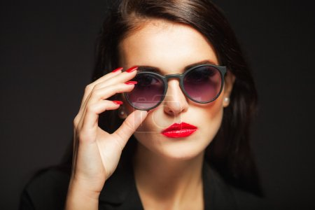 Glamour woman with sunglasses, red lips and nails