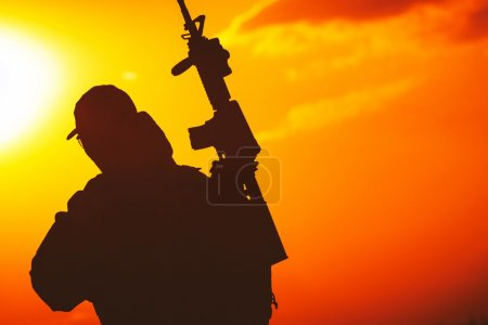 Photo for Modern Equipped Soldier with Rifle Sunset Silhouette. Military Concept - Royalty Free Image