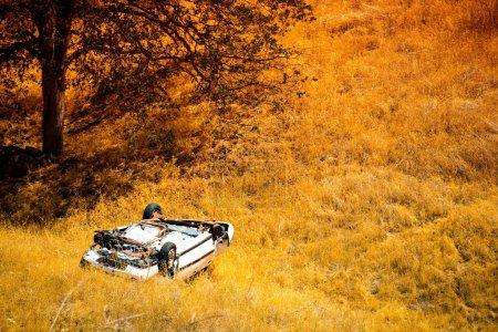 Photo pour Chute Compact Car Crash. White Crashed Car in the Mountain Road Ditch en Californie, États-Unis. Accident de la circulation . - image libre de droit