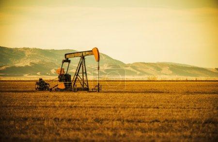 """Photo pour """"Aged Oil Pump on Colorado Prairie with Mountain Hills in the Background"""". Thème Industrie pétrolière . - image libre de droit"""