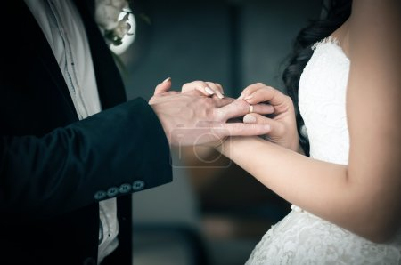 Photo for Bride puts on a wedding ring on grooms finger - Royalty Free Image