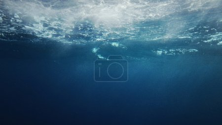Beautiful underwater sea scene view from window porthole with natural light rays