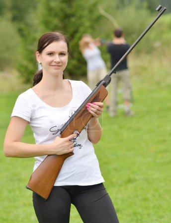 Photo pour Jeune fille visant un fusil pneumatique à l'extérieur - image libre de droit