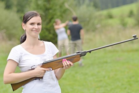 Photo for Girl aiming a pneumatic rifle outdoors - Royalty Free Image