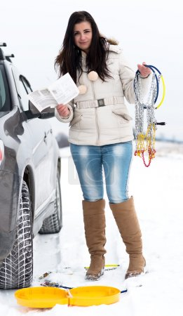 Woman putting winter tire chains on car