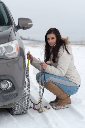 Woman putting winter tire chains on car wheel