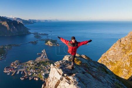 Photo pour Femmes sportives au sommet de la montagne au-dessus de l'océan, village de pêcheurs Reine, Lofoten, Norvège - image libre de droit