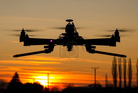 Photo for Hexacopter drone flying in the sunset like an ufo - Royalty Free Image
